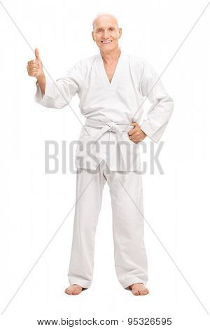 Full length portrait of a senior man in a white kimono giving a thumb up and smiling isolated on white background