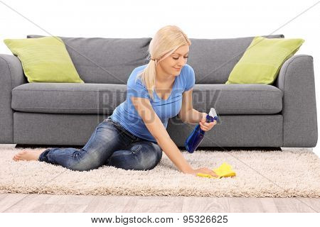 Young woman cleaning a carpet with a rag isolated on white background