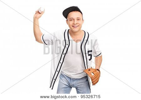 Cheerful young baseball player throwing a baseball and looking at the camera isolated on white background