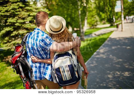 Amorous couple with backpacks walking in urban environment
