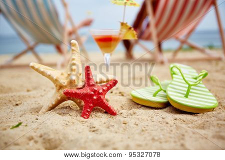 Two sea stars on sandy beach with cocktail and flipflops near by