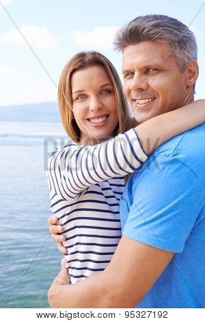 Amorous couple in embrace looking at camera by the sea