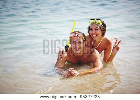 Couple of happy scuba divers lying in water