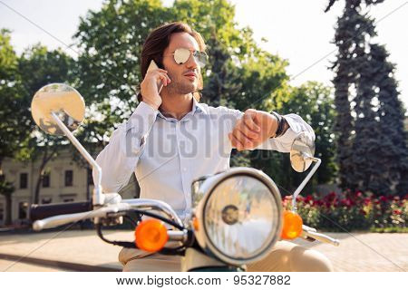 Man talking on the phone and looking on wrist watch outdoors