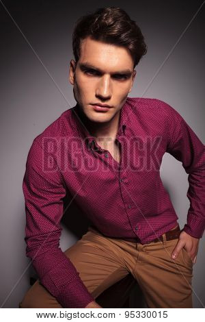 Young handsome casual man sitting on a stool while holding his hand in pocket.