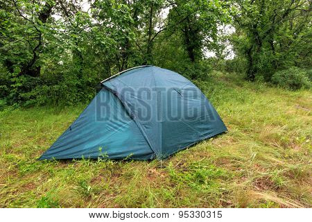 Tourist tent on forest meadow at rainy day