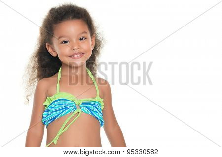 Cute and funny small african-american or hispanic girl wearing a swimsuit isolated on white