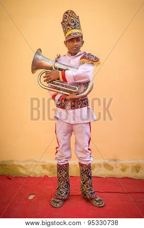 GODWAR REGION, INDIA - 15 FEBRUARY 2015: Young Indian musician dressed in wedding ceremony outfit holds trumpet. Marriages in India are filled with ritual and celebration that go on for several days.