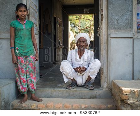 GODWAR REGION, INDIA - 15 FEBRUARY 2015: Young girl stands in doorway of home next to elderly man.