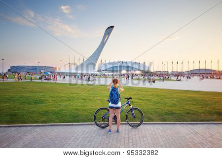 SOCHI, RUSSIA - JUL 27, 2014: Tourists walk in the Olympic park with a bowl of the Olympic flame and the stadium Fischt