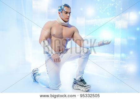 Portrait of a handsome muscular man with perfect body and futuristic make-up and hairstyle demonstrating his strength. Future generation.