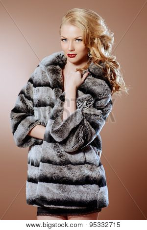 Fashion shot of a beautiful young woman wearing fur coat. Studio shot.