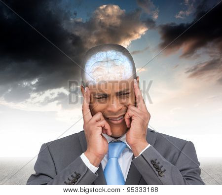 Stressed businessman putting his fingers on his temples against blue sky
