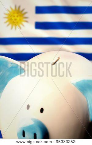 Piggy bank against digitally generated uruguay national flag