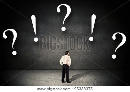Mature businessman looking and considering against black wall