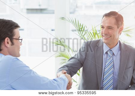 Smiling businessman shaking hands with a co worker in an office