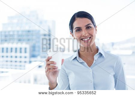 Smiling businesswoman holding disposable cup in an office