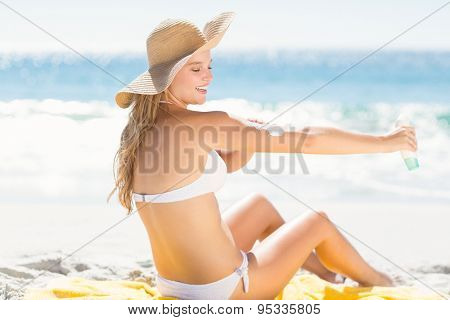 Pretty blonde woman spreading sun tan lotion on her arms at the beach