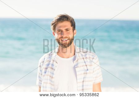 Handsome man looking at camera at the beach