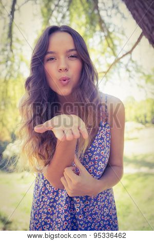 Pretty brunette blowing kiss at camera on a sunny day
