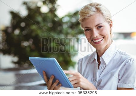 Happy pretty blonde using tablet computer