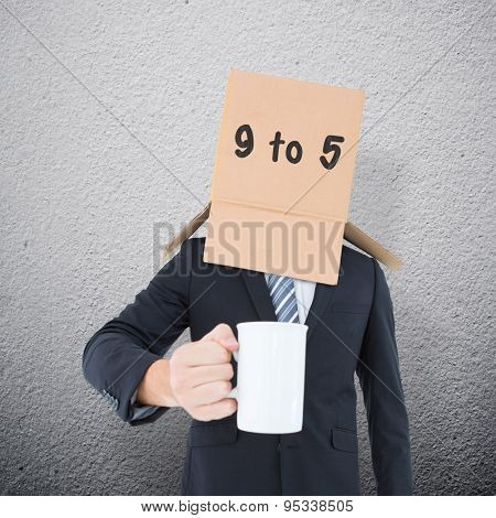 Anonymous businessman with mug against grey wall