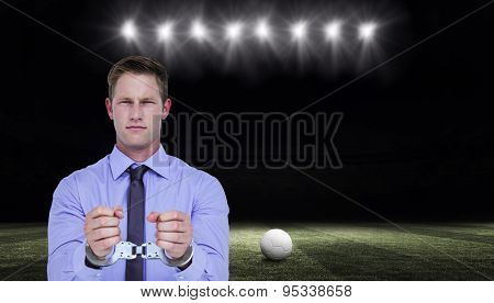 Handsome businessman wearing handcuffs against football pitch at night with ball and lights