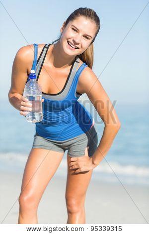 Smiling fit woman looking at camera at the beach