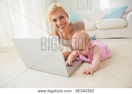 Happy blonde mother with her baby girl using laptop at home in the living room