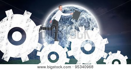Happy businessman leaping with his briefcase against bright moon over city
