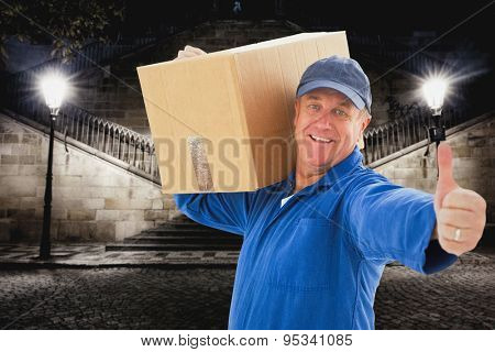 Happy delivery man holding cardboard box against building by night