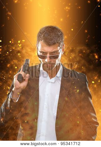Portrait of a man in suit with handgun