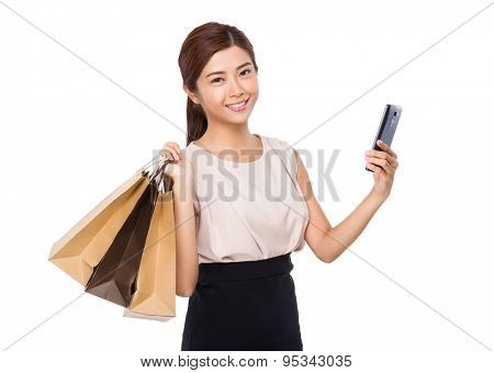 Woman holding shopping bag and mobile phone