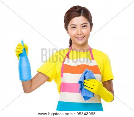 Asian Housewife using bottle spray and rag with plastic gloves