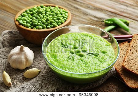 Green pea soup in glass bowl on wooden cutting board with sackcloth, closeup