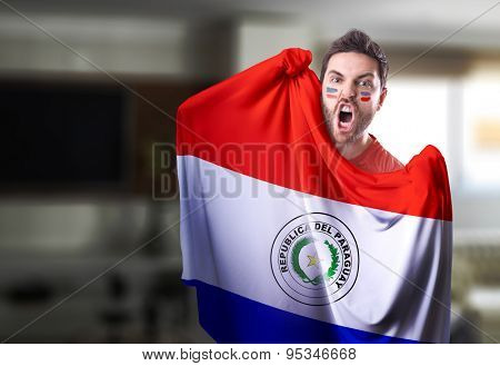 Fan holding the flag of Paraguay at home
