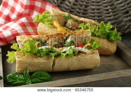 Homemade Spicy Meatball Sub Sandwich on tray, on wooden table background