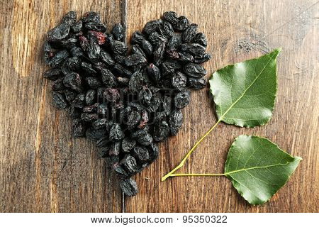 Raisins arranged in heart shape on wooden background