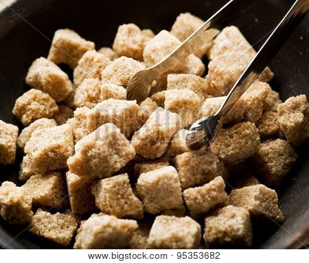 Cubes of cane sugar in the bowl on wooden table.