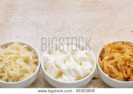 sauerkraut, kimchi and yogurt - popular probiotic fermented food - three ceramic bowl against rustic wood with a copy space