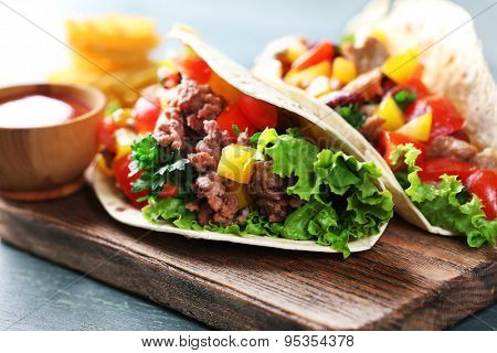 Homemade beef burritos with vegetables and tortilla, on cutting board, on wooden background