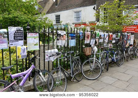 CAMBRIDGE, ENGLAND - MAY 13: Row of Bicycles Locked Up Along Iron Fence Covered with Advertisement Posters, Cambridge, England