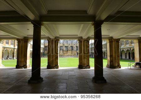 CAMBRIDGE, ENGLAND - MAY 13: View of Sunny Green Courtyard from Inside Historical Trinity College Building Colonnade, University of Cambridge, England on May 13, 2015