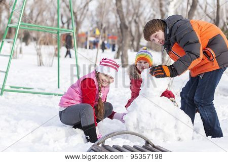 Children in winter park having fun and playing snowballs