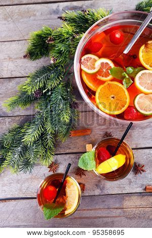 Sangria in bowl and glasses with Christmas decoration on wooden table close up