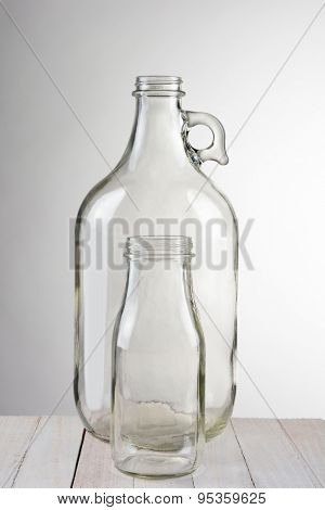 Two empty glass bottles, a small bottle in front of a larger container. Vertical format against a light to dark gray background. The bottles are set on a rustic wood table.