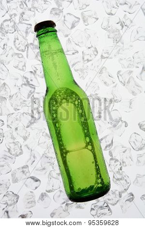 A single green bottle of beer backlit on a bed of ice. The bottle has no label. Vertical Format.