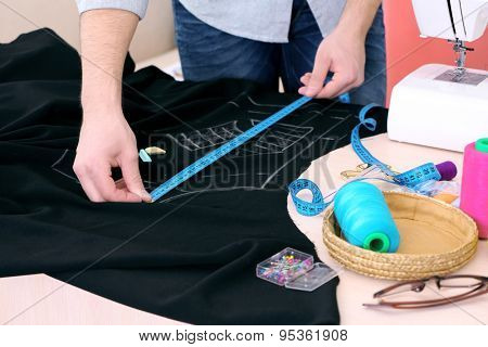 Male dressmaker drawing line on fabric on table close-up