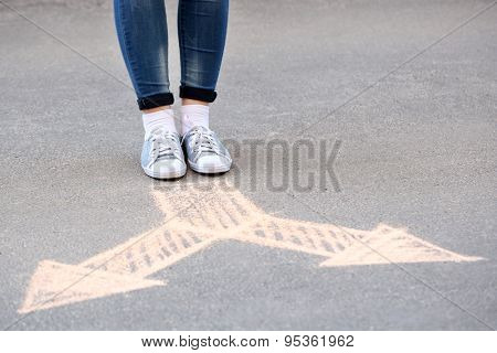 Female feet and drawing arrows on pavement background