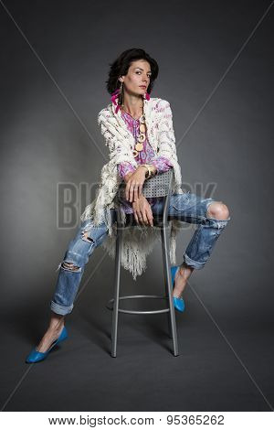 Beautiful brunette girl in worn jeans and knitted shawl sitting on a chair. Studio portrait.